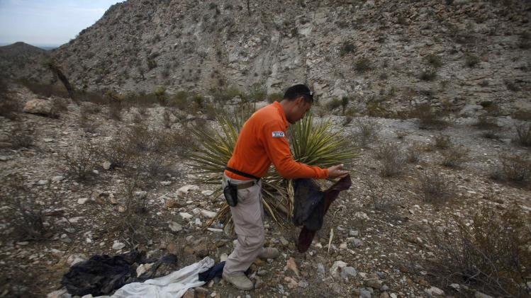 Grupo Beta member looks at discarded clothing while searching in the mountains between Mexico and the U.S. for potential border crossers during a patrol on the outskirts of Ciudad Juarez