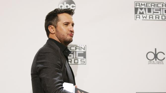 Luke Bryan poses with his award during the 42nd American Music Awards in Los Angeles