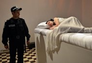 "A policeman looks at sleeping woman during a performance at Ukraine's National Art Museum in Kiev. A performance called ""Sleeping Beauty"" allows visitors to kiss a series of volunteer Sleeping Beauties, but only if they signed an undertaking to marry the women if she ""wakes up"""