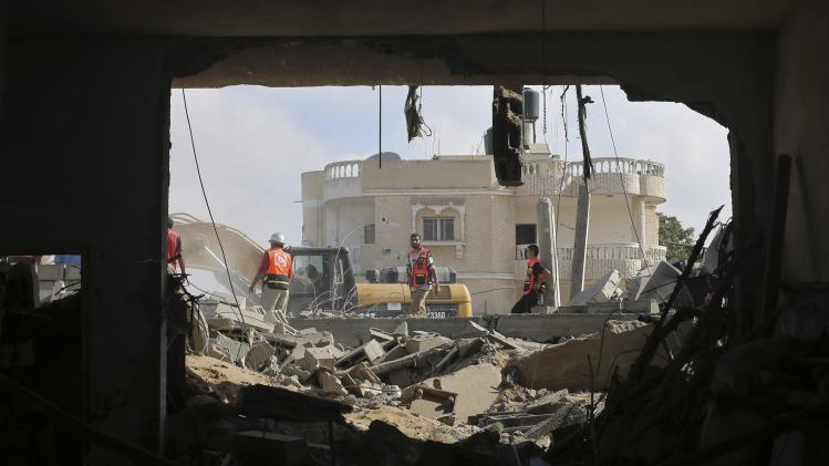 Palestinian rescue workers search for victims under the rubble of a house which witnesses said was destroyed by an Israeli air strike during an Israeli ground offensive east of Khan Younis in the southern Gaza Strip
