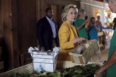 Democratic presidential candidate Hillary Clinton picks out fresh corn during a visit to Dimond Hill Farm in Hopkinton