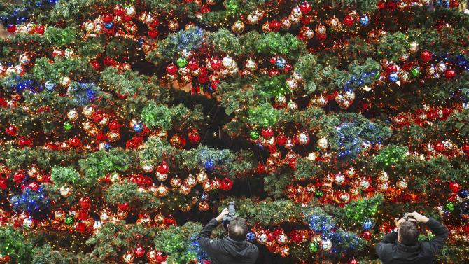 Two people take pictures of a Christmas tree at the Marlene-Dietrich-Platz in Berlin