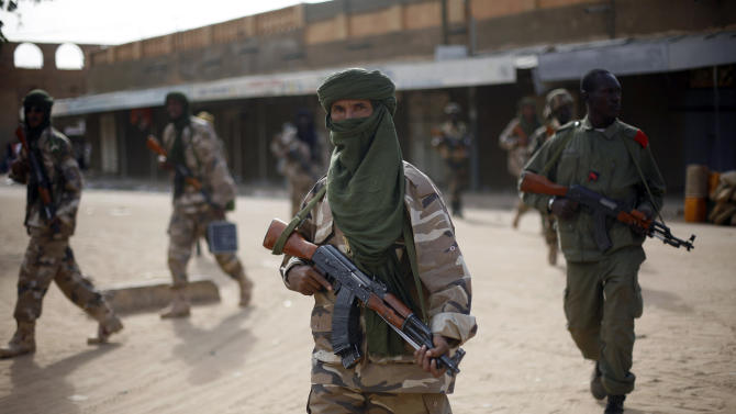 """Chadian soldiers patrol the streets vacated by Islamic extremists  in Gao, Northern Mali, Tuesday Jan. 29, 2013, days after Malian and French military forces closed in and retook the town from Islamist rebels. Earlier Tuesday, four suspected extremists were arrested after being found by a youth militia calling themselves the """"Gao Patrolmen"""". Malian soldiers prevented the mob from lynching them. (AP Photo/Jerome Delay)"""