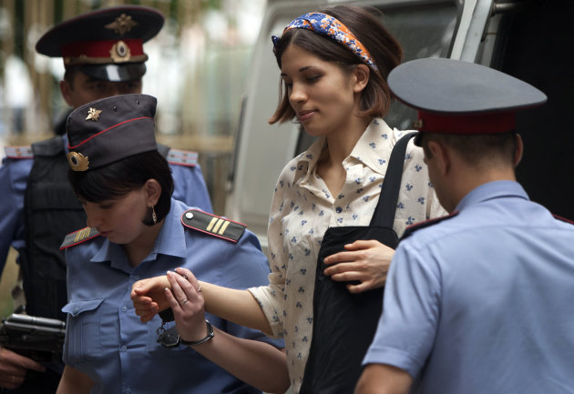 "Nadezhda Tolokonnikova, centre, a member of feminist punk group Pussy Riot is escorted to a court room in Moscow, Russia, Tuesday, Aug. 7, 2012. Russia's President Vladimir Putin on Thursday criticized the feminist punk rockers facing trial for performing a ""punk prayer"" against him at Moscow's main cathedral, but said that a punishment for them shouldn't be too severe. (AP Photo/Alexander Zemlianichenko)"