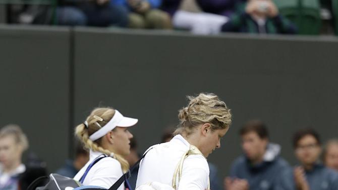 Kim Clijsters of Belgium, right, leaves the court with Angelique Kerber of Germany following a fourth round singles match which she lost at the All England Lawn Tennis Championships at Wimbledon, England, Monday, July 2, 2012. (AP Photo/Alastair Grant)