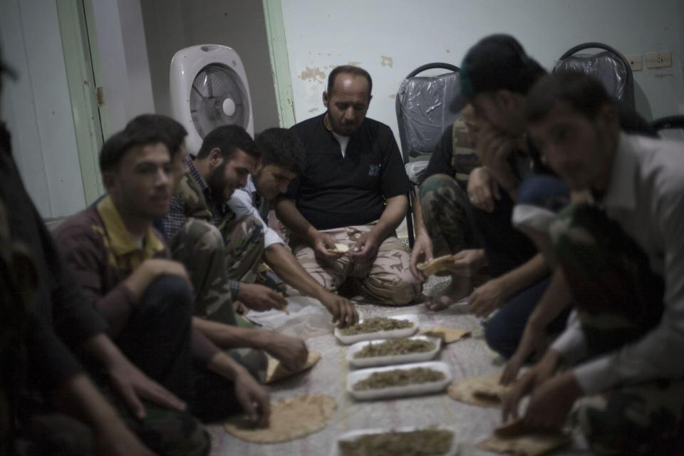 In this Sunday, Sept. 23, 2012 photo, Free Syrian Army fighters have lunch before leaving their headquarters in Aleppo, Syria. (AP Photo/ Manu Brabo)