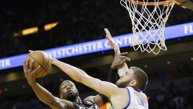 Philadelphia 76ers' Spencer Hawes (00) tries to block Miami Heat's Dwyane Wade (3) during the first half of a NBA basketball game in Miami, Friday, March 8, 2013. (AP Photo/J Pat Carter)