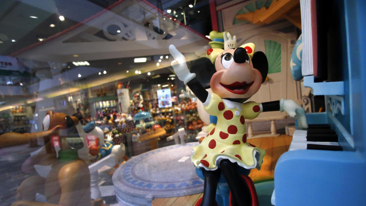 In this Friday, Jan. 31, 2014, photo, a Minnie Mouse character plays piano in a Disney Store display window in Saugus, Mass. Walt Disney Co. reports quarterly financial results after the market closes on Wednesday, Feb. 5, 2014. (AP Photo/Elise Amendola)