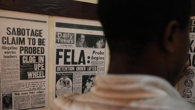 A man stands amid reproduced newspaper front pages with headlines about singer Fela Anikulapo-Kuti in a museum about the musician in Lagos, Nigeria, on Monday, Oct. 15, 2012. The family of late Afrobeat singer Fela Anikulapo-Kuti celebrated the opening of the Kalakuta Museum on Monday in Lagos in the home the musician once lived in. The opening of the museum comes during Felabration, an annual music festival honoring the singer. (AP Photo / Jon Gambrell)