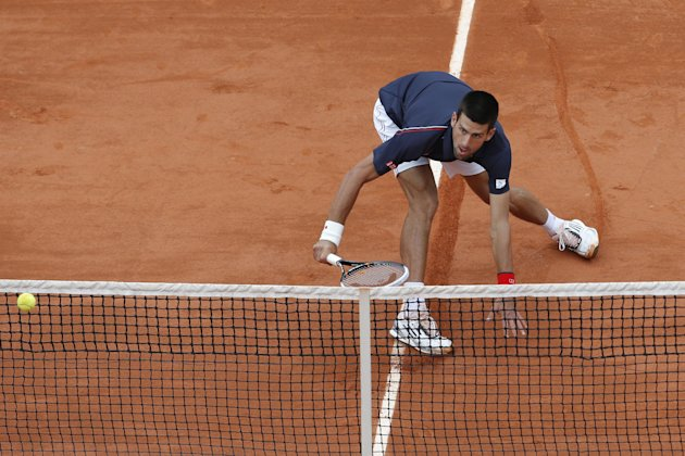 Novak Djokovic of Serbia slides to the net to return in his fourth round match against Andreas Seppi of Italy at the French Open tennis tournament in Roland Garros stadium in Paris, Sunday June 3, 201