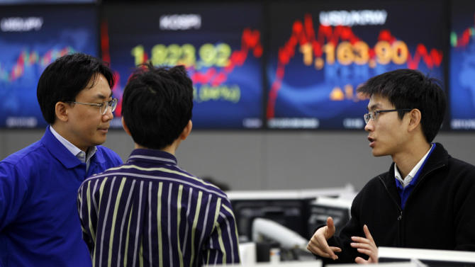 Currency traders talk each other at the foreign exchange dealing room of the Korea Exchange Bank headquarters in Seoul, South Korea, Monday, Jan. 9, 2012. Asian stocks dropped Monday, ignoring signs of job improvement in the U.S., as traders continued to fret about Europe's unfolding sovereign debt drama. South Korea's Kospi fell 1.1 percent to 1,822.42. (AP Photo/Lee Jin-man)
