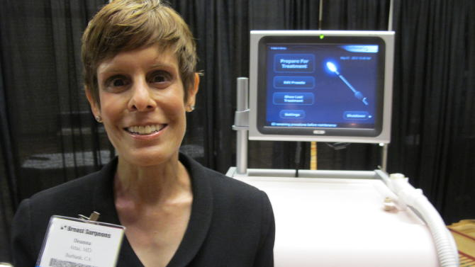 Dr. Deanna Attai, who is on the board of directors for American Society of Breast Surgeons, stands in front of cryoablation machine at the American Society of Breast Surgeons conference on May 1, 2013 in Chicago. The machine uses liquid nitrogen to freeze some kinds of breast cancer tumors.  Treating breast cancer almost always involves surgery, and for years the choice was just having the lump or the whole breast removed. Now, new approaches are dramatically changing the way these operations are done, giving women more options, faster treatment, smaller scars, fewer long-term side effects and better cosmetic results. (AP Photo/Carrie Antlfinger)