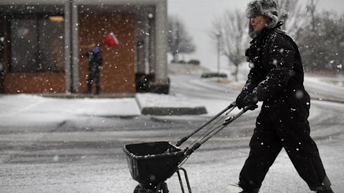 """Ann Dass of Bent Mountain Va. spreads salt on a business parking lot in Christiansburg Va. Thursday Jan. 17 2013. Dass and her brother David Taylor, left background, are part of Acme Snow and Ice Removal and were trying to get the upper hand on the oncoming winter storm. """"I'm sure we'll be back"""" said Dass about the quickly accumulating snowfall and the challenge of removing it.  (AP PHOTO/The Roanoke Times, Matt Gentry) (AP Photo/The Roanoke Times, )  LOCAL TV OUT; SALEM TIMES REGISTER OUT; FINCASTLE HERALD OUT;  CHRISTIANBURG NEWS MESSENGER OUT; RADFORD NEWS JOURNAL OUT; ROANOKE STAR SENTINEL OUT"""