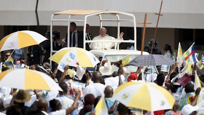 Pope Francis waves as he arrives to lead a mass at the Bangui stadium