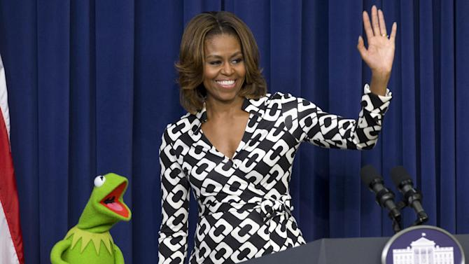 "First lady Michelle Obama waves goodbye with Kermit the Frog after speaking to children of military families in the South Court Auditorium of the Eisenhower Executive Office Building on the White House complex, Wednesday, March 12, 2014, before a screening of Disney's ""Muppets Most Wanted"" movie as part of the Joining Forces initiative. (AP Photo/Jacquelyn Martin)"