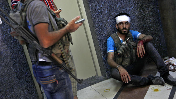 An injured Syrian fighter sits on the ground after being treated at a field hospital in Aleppo, Syria, Friday, Aug. 17, 2012. Rebel footholds in Aleppo have been the target of weeks of Syrian shelling and air attacks as part of wider offensives by President Bashar Assad's regime. Rebels have been driven from some areas, but the report of clashes near the airport suggests the battles could be shifting to new fronts. (AP Photo/ Khalil Hamra)
