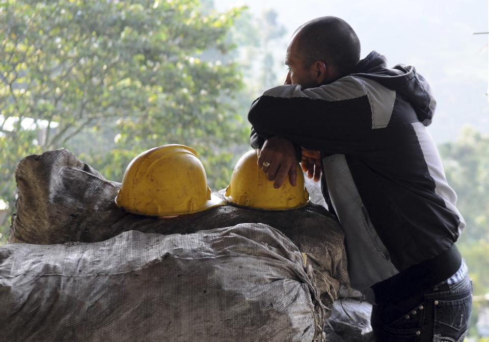 "A miner rests on a helmet sitting on bags of charcoal outside the ""El Desespero"" coal mine in Angelopolis, Colombia, Thursday March 8, 2012.  At least four miners were killed when water flooded and collapsed the small mine on Wednesday. Five others are still missing. (AP Photo/Luis Benavides)"