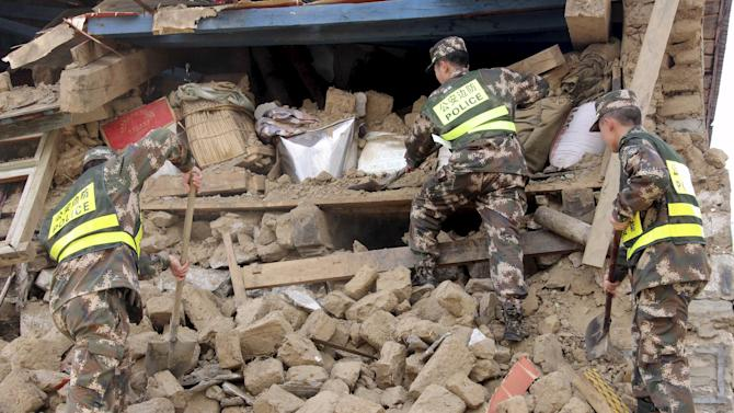 Police search ruins after a 7.9-magnitude earthquake hit Nepal on Saturday, in Gyirong county