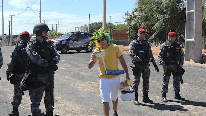 A soccer fan crosses a police line as he makes his way to the Castelao stadium, in Fortaleza, Brazil, Wednesday, June 19, 2013. In this northeastern Brazilian city, an estimated 15,000 protesters clashed with police trying to prevent them from reaching the Castelao stadium before Brazil's game with Mexico in the Confederations Cup soccer tournament. (AP Photo/Andre Penner)