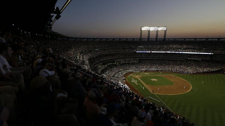 Fans watch the MLB All-Star baseball game as the sun sets, on Tuesday, July 16, 2013, in New York. (AP Photo/Julio Cortez)