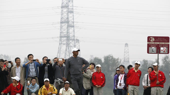 Fans take photos as Tiger Woods of the United States follows a drive by Rory McIlroy of Northern Ireland during their 18-hole medal-match at the Lake Jinsha Golf Club in Zhengzhou, in central China's Henan province, Monday, Oct. 29, 2012. Rory McIlroy shot a 5-under 67 to beat Tiger Woods by one stroke in a head-to-head, 18-hole exhibition match between the world's two top-ranked golfers. (AP Photo/Alexander F. Yuan)