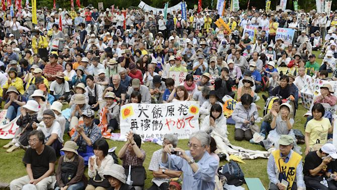 "In this June 17, 2012 photo, people gather for a rally in Fukui city to protest against the restart of two nuclear reactors in Ohi town, Fukui prefecture, western Japan. Public opposition to resuming operations remains high, however, because of the March 2011 crisis at Fukushima Dai-ichi plant that turned into the world's worst atomic disaster since Chernobyl and a lingering distrust of an industry widely seen as opaque. The banner reads: Please stop reactivating the Ohi nuclear plant."" (AP Photo/Kyodo News) JAPAN OUT, MANDATORY CREDIT, NO LICENSING IN CHINA, HONG KONG, JAPAN, SOUTH KOREA AND FRANCE"