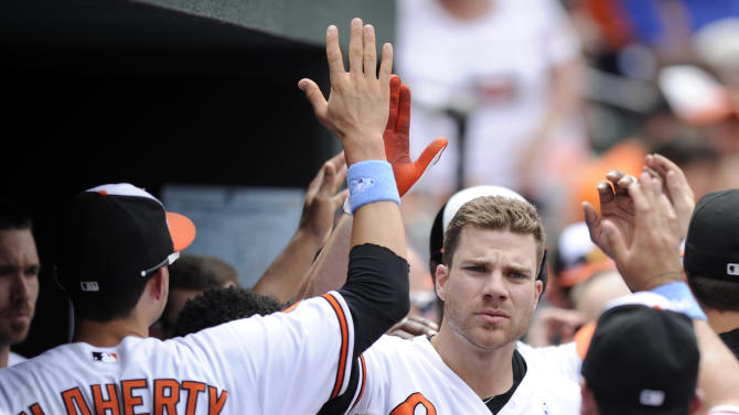 Baltimore Orioles' Chris Davis, center, celebrates his two-run home run in the dugout with Ryan Flaherty (3) and others in the dugout during the third inning of a baseball game against the Boston Red Sox, Sunday, June 16, 2013, in Baltimore. (AP Photo/Nick Wass)