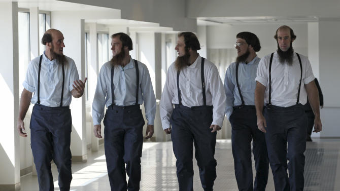Members of the Amish leave the U.S. Federal Courthouse Tuesday, Aug. 28, 2012, in Cleveland. A breakaway religious group spent months planning hair-cutting attacks against followers of their Amish faith, U.S. prosecutors said Tuesday as they laid out their case against 16 people charged with hate crimes. Such hair-cuttings are considered deeply offensive in the traditional Amish culture. (AP Photo/Tony Dejak)