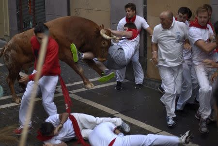 A runner is tossed by a Miura fighting bull at the San Fermin festival in Pamplona