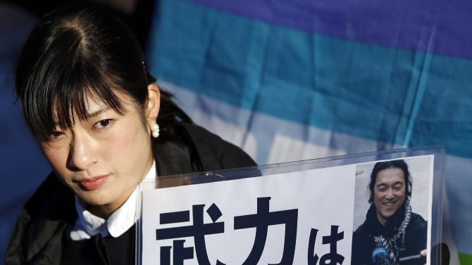 Woman holds a portrait of Japanese journalist Kenji Goto on a placard during a rally against Japan's Prime Minister Shinzo Abe in front of Abe's official residence in Tokyo