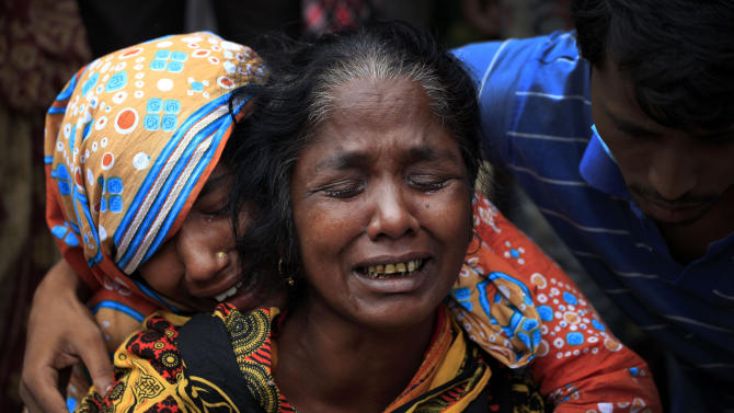 A woman is comforted as she grieves after identifying the body of her daughter, a victim of the garment factory collapse, Sunday, May 5, 2013, in Savar, near Dhaka, Bangladesh. The death toll from the collapse of a shoddily built garment-factory building in Bangladesh continued its horrifying climb, reaching more than 600 on Sunday with little sign of what the final number will be. The disaster is likely the worst garment-factory accident ever, and there have been few industrial accidents of any kind with a higher death toll. (AP Photo/Wong Maye-E)