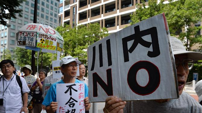 """An anti-nuclear protester holds a placard reading """"Sendai NO"""" during a rally in Tokyo on July 16, 2014"""