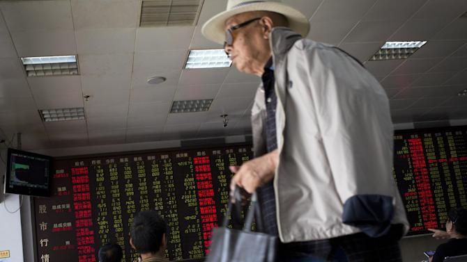 A man leaves as stock investors monitor the stock prices at a brokerage house in Beijing, China, Wednesday, July 8, 2015. China's central bank has promised more credit to finance stock trading in the latest move aimed at stopping a plunge in stock prices that has prompted hundreds of companies to suspend trading in their shares. (AP Photo/Andy Wong)