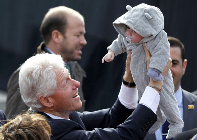 Former President Bill Clinton holds up a baby after speaking in New Hampshire