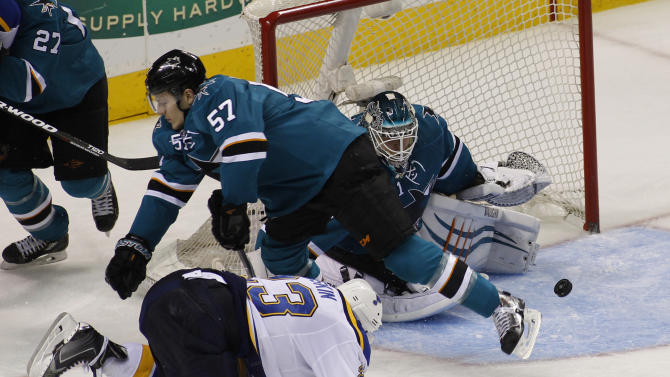 San Jose Sharks' Tommy Wingels, center, falls forward while defending, between St. Louis Blues' Dmitrij Jaskin, front, and Sharks' goalie Antti Niemi during the third period of an NHL hockey game, Saturday, Dec. 20, 2014, in San Jose, Calif. The Sharls beat the Blues in overtime, 3-2. (AP Photo/George Nikitin)