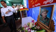 Vu Dinh Son (L) cries next to his late father Vu Dinh Doan's protrait during a ceremony where his personal documents including a frayed diary were handed over to his family in northern province of Hai Duong