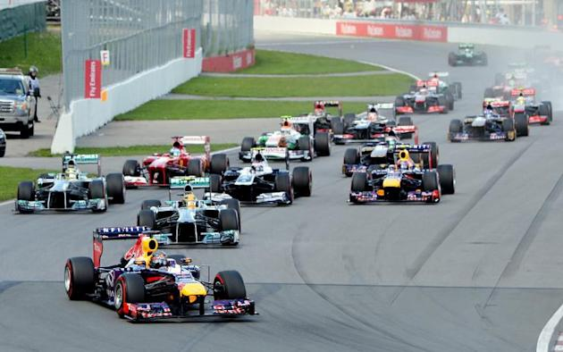 Red Bull driver Sebastian Vettel of Germany (L) leads the grid into the first turn at the start of the Canadian Formula One Grand Prix at the Circuit Gilles Villeneuve in Montreal on June 9, 2013