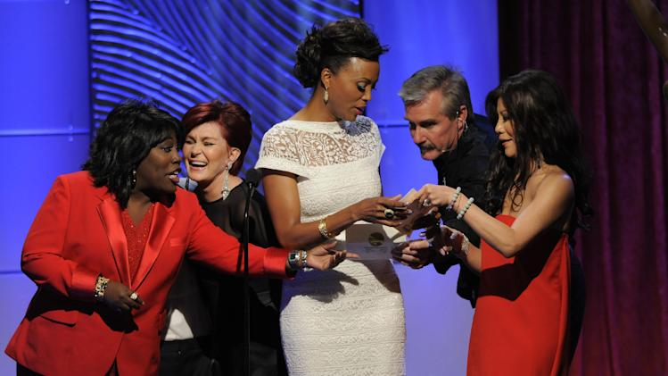 A stagehand, second from right, hands the correct winner results to presenters, from left, Sheryl Underwood, Sharon Osbourne, Aisha Tyler and Julie Chen on stage at the 40th Annual Daytime Emmy Awards on Sunday, June 16, 2013, in Beverly Hills, Calif. They were presenting the award for outstanding informative talk show. (Photo by Chris Pizzello/Invision/AP)