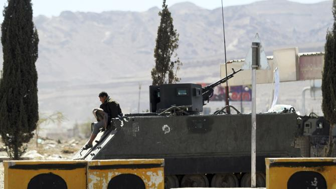 A Houthi fighter sits on top of a military truck which was seized from the army during recent clashes, outside an entrance to the presidential palace in Sanaa
