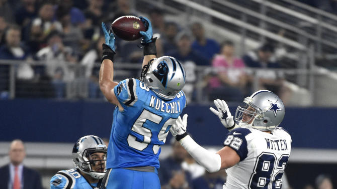 Carolina Panthers middle linebacker Luke Kuechly (59) intercepts a pass intended for Dallas Cowboys tight end Jason Witten (82) as Kurt Coleman (20) watches during the first half of an NFL football game, Thursday Nov. 26, 2015, in Arlington, Texas. Kuechly returned the interception back for a touchdown. (AP Photo/Michael Ainsworth)