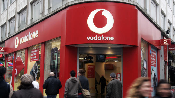 FILE - In this Tuesday, Feb. 24, 2009 file photo, people walk by a Vodafone branch in central London. Vodafone, one of the world's largest cellphone companies, on Friday, June 6, 2014 revealed the scope of government snooping into phone networks, saying authorities in some countries are able to directly access an operator's network without seeking permission. (AP Photo/Sang Tan, File)