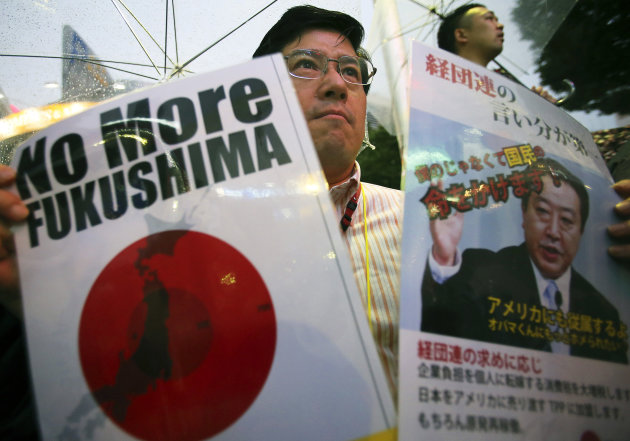 A participant holds a slogan and a photo of Japanese Prime Minister Yoshihiko Noda during a rally protesting the restart of Ohi nuclear power plant, in Tokyo, Sunday, July 1, 2012. Noda ordered the restarts of the plant&#39;s two reactors last month, saying people&#39;s living standards can&#39;t be maintained without nuclear energy. Protesters were against a return to nuclear power because of safety fears after the Fukushima accident and demanded the resignation of Noda. (AP Photo/Shizuo Kambayashi)