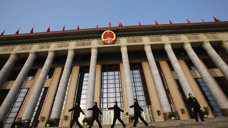 PLA soldiers in plain clothes march in front of the Great Hall of the People, the venue of the annual session of China's parliament, in Beijing