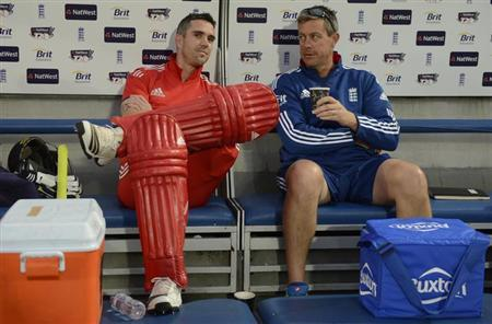 England's Kevin Pietersen and coach Ashley Giles (right) sit in the dugout as the rain falls before the second T20 international cricket match against New Zealand was abandoned at the Oval cricket gro