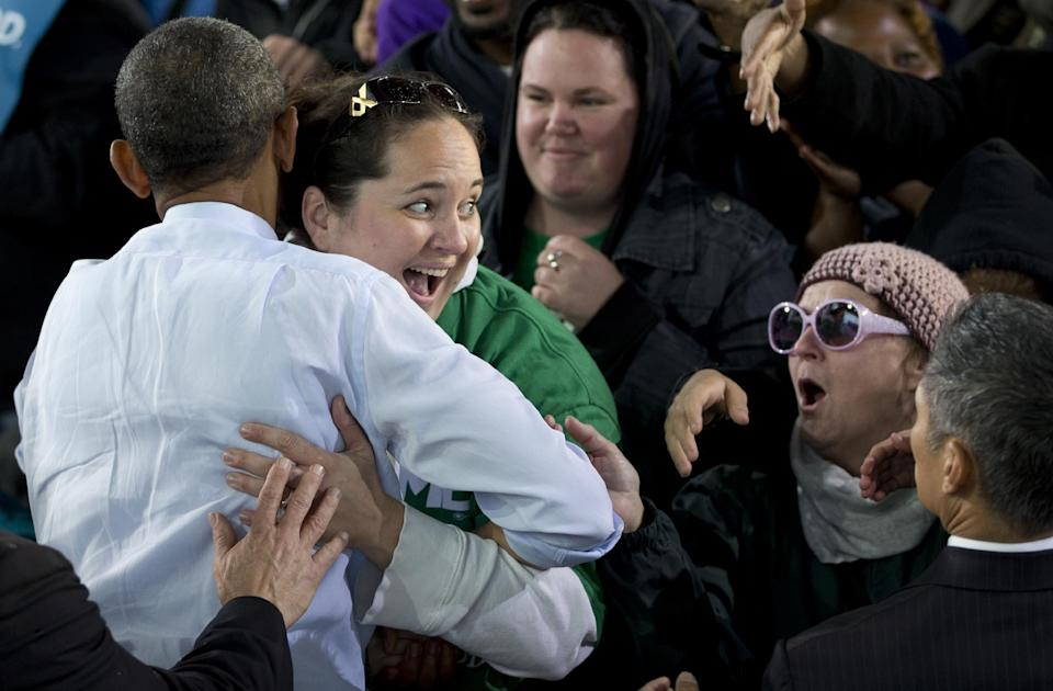President Barack Obama is hugged by a woman as he greets people at a campaign event at the Summerfest Grounds at Henry Maier Festival Park, Saturday, Sept. 22, 2012, in Milwaukee. (AP Photo/Carolyn Kaster)