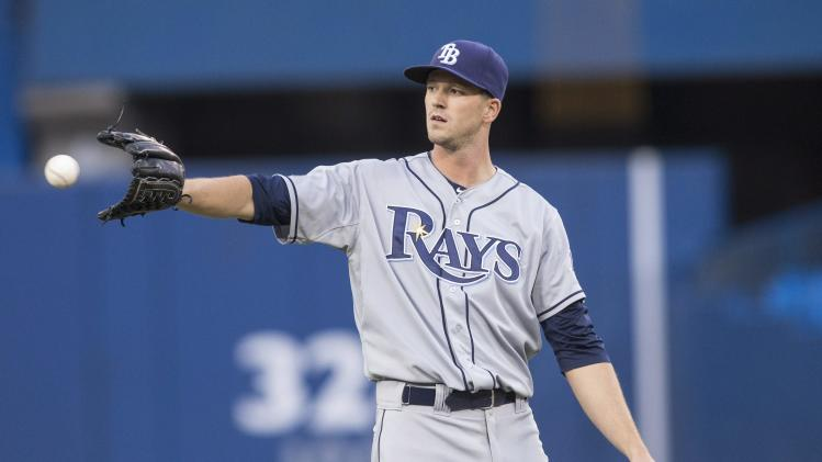Tampa Bay Rays starting pitcher Drew Smyly takes a ball from the infield as he works against Toronto Blue Jays during the second inning of a baseball game, Friday, Aug. 22, 2014 in Toronto. (AP Photo/The Canadian Press, Chris Young)