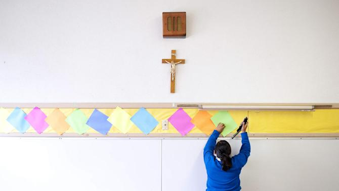 This July 18, 2012, photo shows Adriana Landeros stapling colored paper to the wall of a classroom after summer school at Our Lady of Lourdes in Los Angeles. Many students, such as Landeros, volunteer their time after class to help improve the school in hopes of building enrollment. (AP Photo/Grant Hindsley)