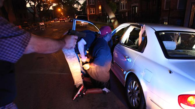 In a June 9, 2012 photo, on Chicago's West side, a high speed pursuit following four suspected gang members ended with the Chicago Police gang unit questioning and arresting one of them on an outstanding warrant. These pursuits are becoming more common as Chicago's homicides have ticked up over 50 percent this year over last. (AP Photo/Robert Ray)