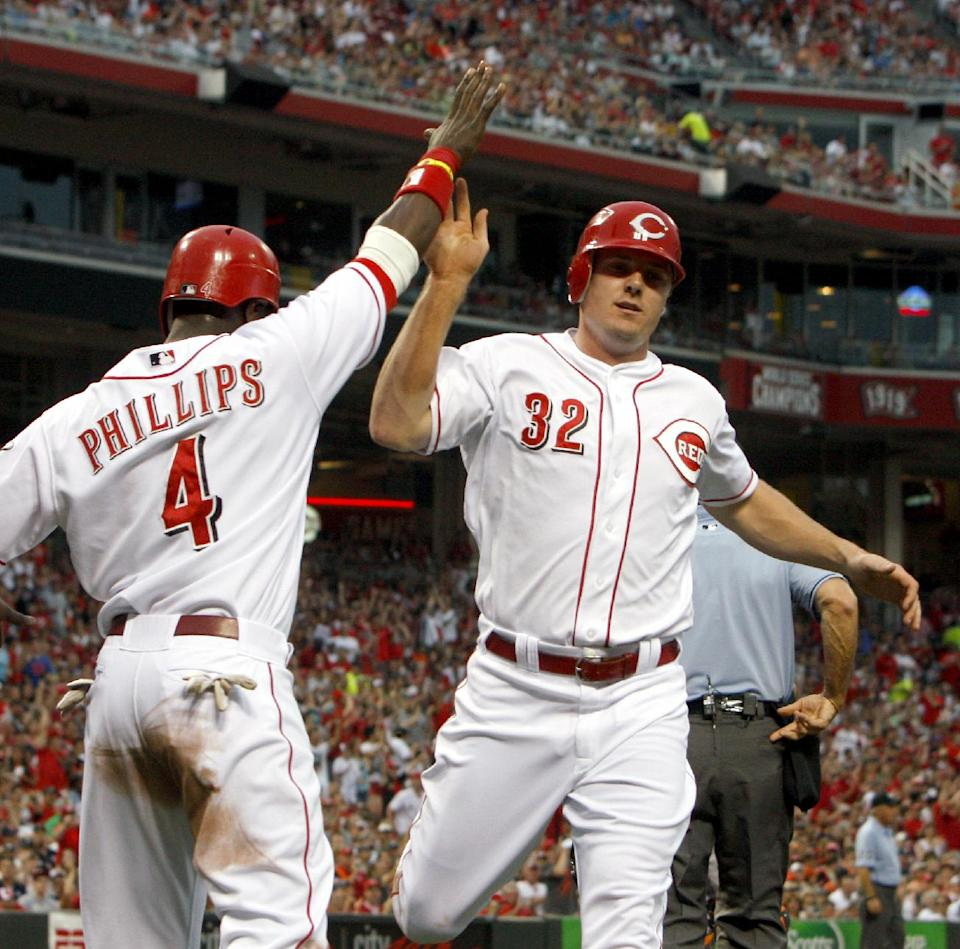 Cincinnati Reds' Jay Bruce (32) is congratulated by Brandon Phillips (4) after they scored on a single hit by Todd Frazier off Detroit Tigers starting pitcher Drew Smyly in the second inning of a baseball game, Sunday, June 10, 2012, in Cincinnati. (AP Photo/David Kohl)