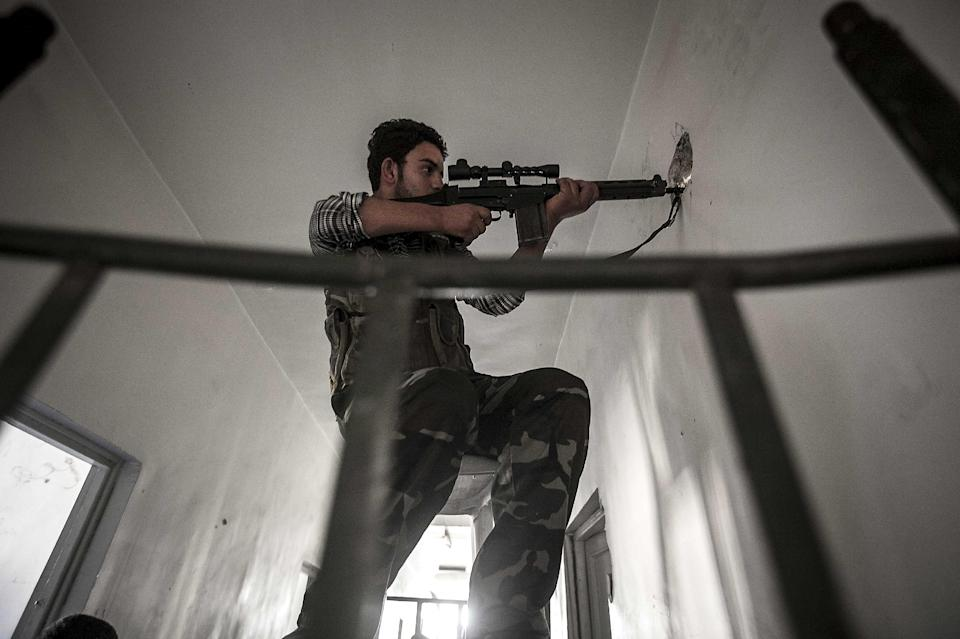 In this Tuesday, Oct. 30, 2012 photo, a rebel sniper belonging to the Liwa Al-Fatah keeps an eye on an enemy position from a school building during skirmishes with the Syrian army in the nearby Bustan Al-Pasha front line in Aleppo, Syria. (AP Photo/Narciso Contreras)